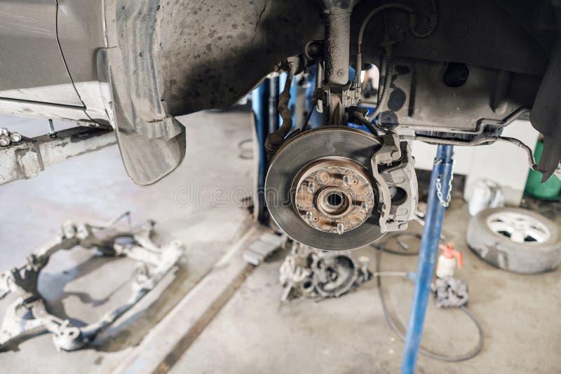 Mecánico de coche que examina la rueda de coche y el detalle de la suspensión de la reparación Automóvil levantado en la gasoline foto de archivo
