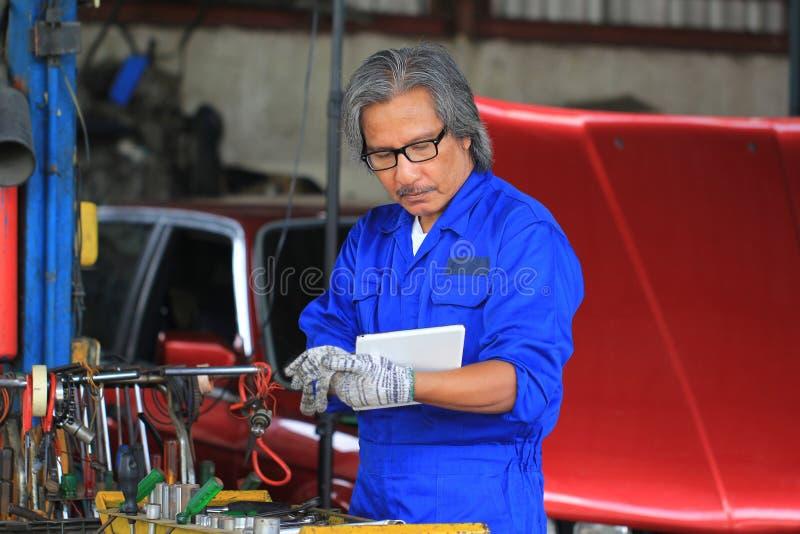 Mecánico de coche que sostiene la tableta digital en servicio de reparación auto fotos de archivo