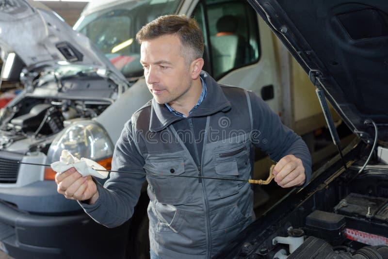 Mecánico de coche que substituye el aceite en el motor en garaje imagen de archivo