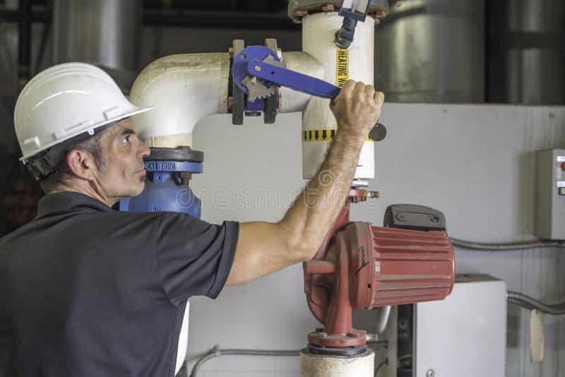 Mecánico de la HVAC que cierra en una válvula de la caldera imagen de archivo