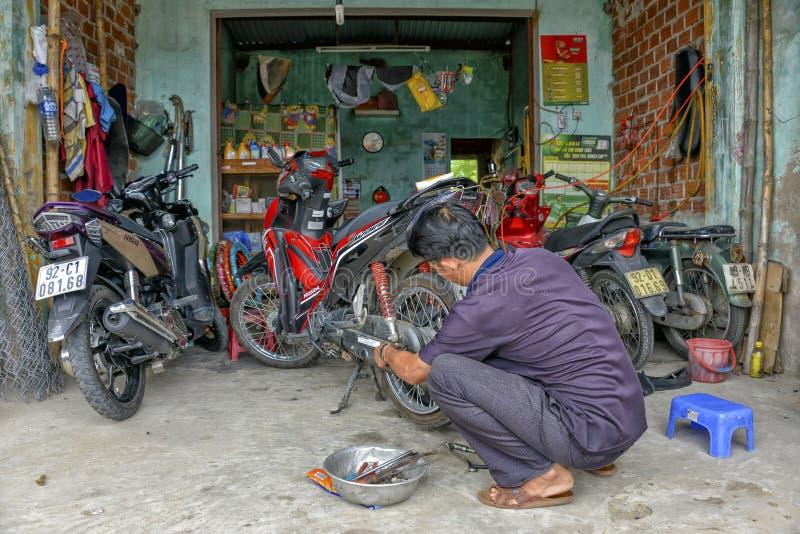 Mecánico de la motocicleta que repara la vespa del neumático desinflado imagen de archivo
