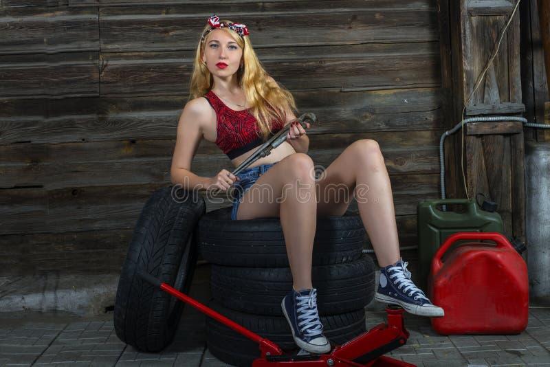 Mecánico de la muchacha con el enchufe y las ruedas foto de archivo libre de regalías