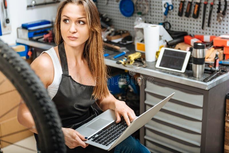 Mecánico de sexo femenino atractivo que usa el ordenador portátil en el taller fotos de archivo libres de regalías