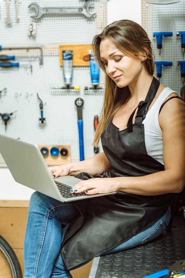 Mecánico de sexo femenino implicado que practica surf Internet en el taller imagenes de archivo