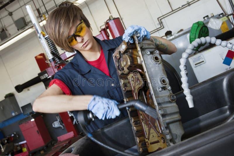 Mecánico de sexo femenino joven que trabaja con el soplete en pieza de maquinaria del vehículo en taller de reparaciones auto foto de archivo