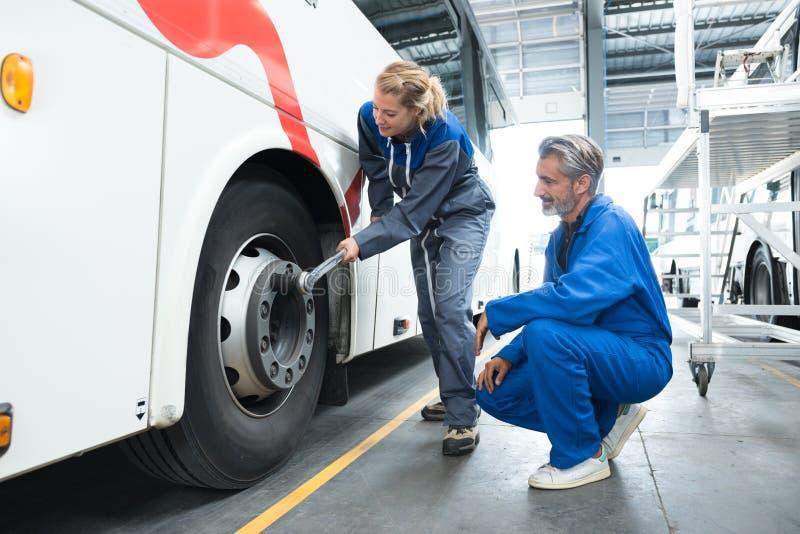 Mecánico de sexo femenino que usa la llave del tonque en nueces de la rueda del autobús fotografía de archivo