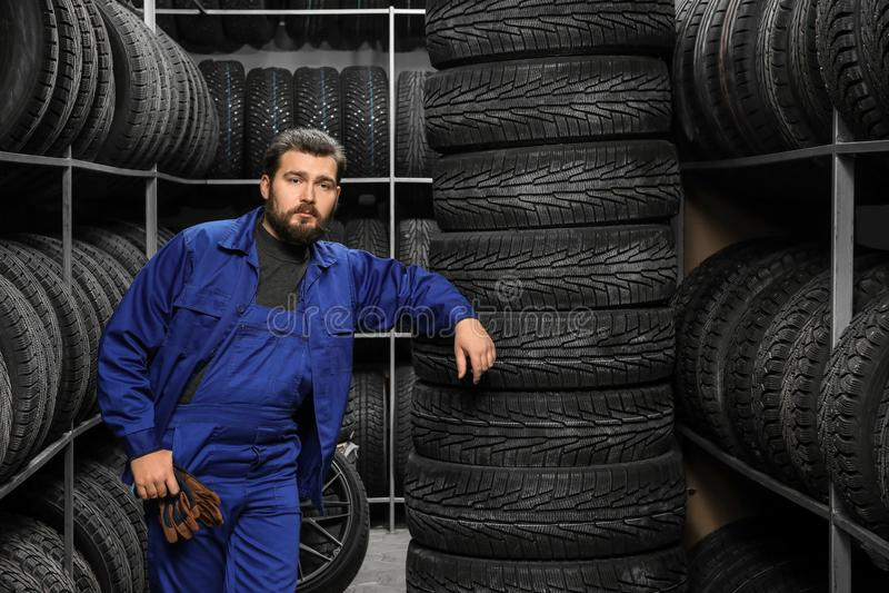 Mecánico de sexo masculino cerca de los neumáticos imagen de archivo libre de regalías