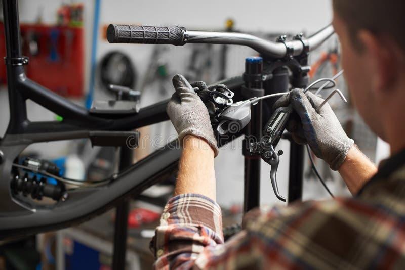 Mecánico de sexo masculino que trabaja en el taller de reparaciones de la bicicleta usando las herramientas imágenes de archivo libres de regalías
