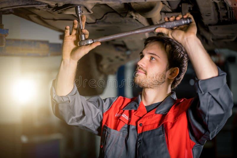 Mecánico debajo del coche en neumático examing del garaje y condiciones técnicas imagenes de archivo