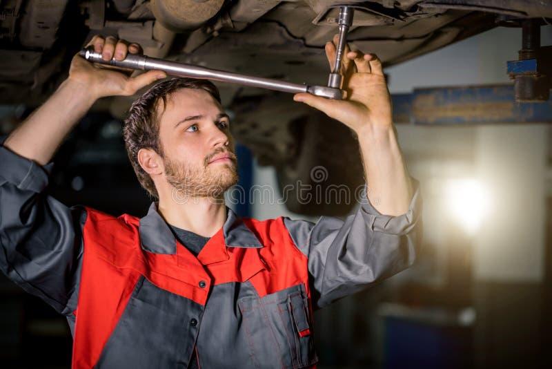 Mecánico debajo del coche en neumático examing del garaje y condiciones técnicas imagen de archivo