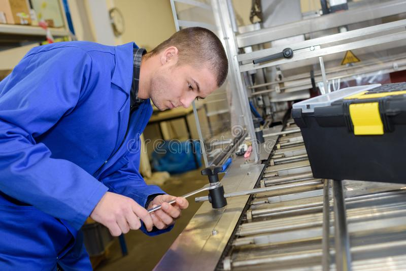 Mecánico del aprendiz que trabaja en la fábrica foto de archivo