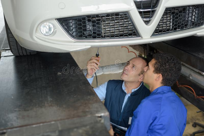 Mecánico del aprendiz que trabaja por debajo el coche con el profesor fotos de archivo