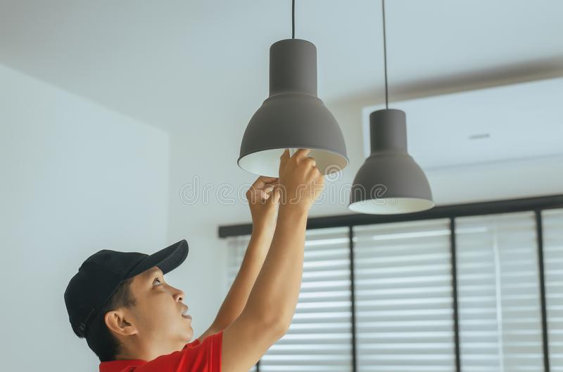 Mecánico del hombre de las manos que cambia con la bombilla de la nueva lámpara del LED, concepto del ahorro de energía foto de archivo