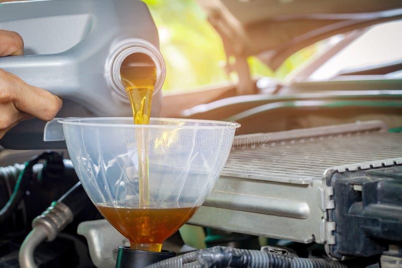 Mecánico del mantenimiento del coche que vierte el nuevo lubricante del aceite en el motor de coche Foco selectivo fotografía de archivo libre de regalías