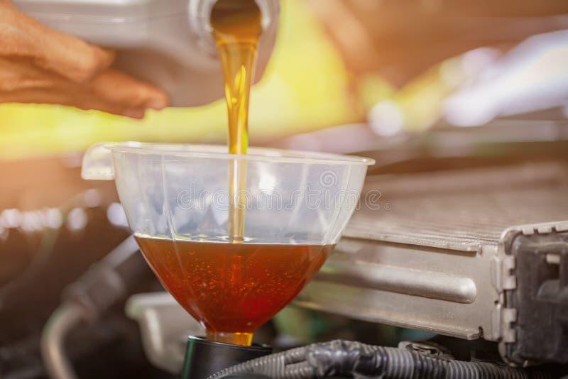 Mecánico del mantenimiento del coche que vierte el nuevo lubricante del aceite en el motor de coche Foco selectivo imágenes de archivo libres de regalías