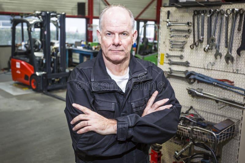 Mecánico en garaje de la carretilla elevadora imágenes de archivo libres de regalías