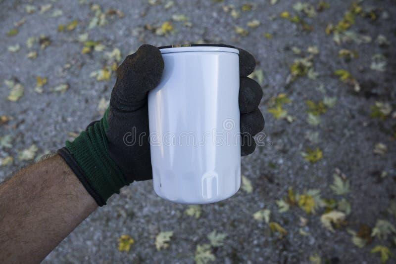 Mecánico Examing un filtro de aceite largo del estilo imagen de archivo