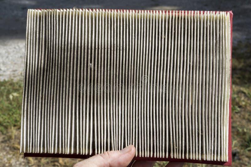Mecánico Examing un filtro de aire sucio foto de archivo