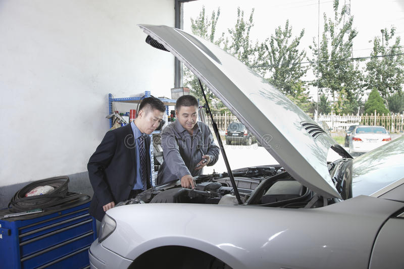 Mecánico Explaining al cliente y mirada del garaje del coche con la capilla abierta fotografía de archivo libre de regalías
