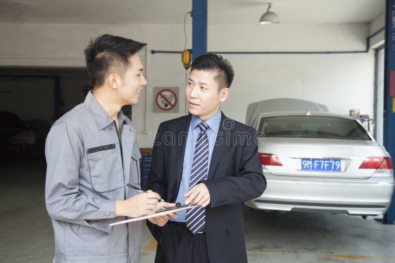 Mecánico Explaining del garaje al cliente, mostrándole el Bill fotos de archivo