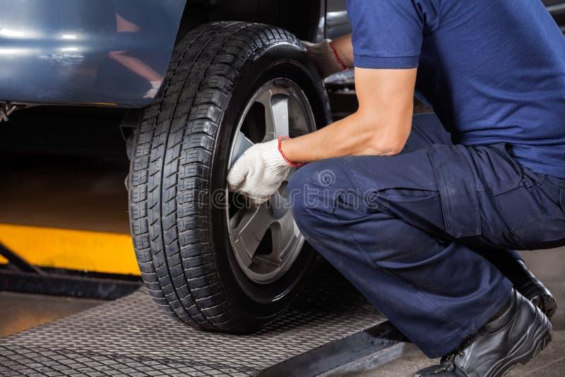Mecánico Fixing Car Tire en el taller de reparaciones imagen de archivo
