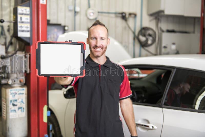 Mecánico hermoso basado en el coche en taller de reparaciones auto con la tableta a mano foto de archivo libre de regalías