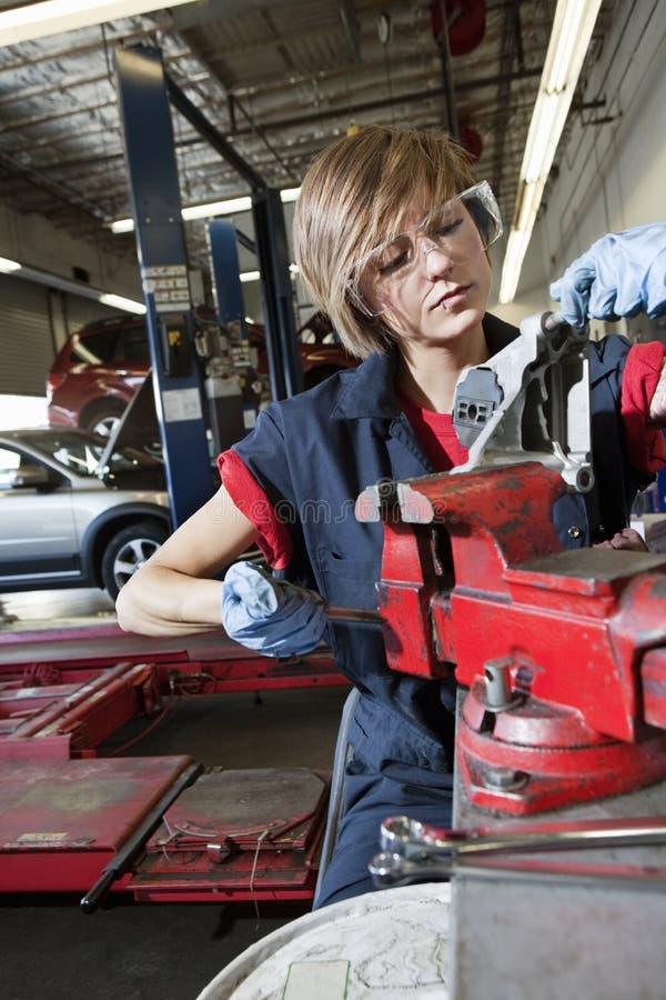Mecánico joven en la ropa protectora que concentra en la reparación de la pieza de la máquina en garaje fotos de archivo libres de regalías