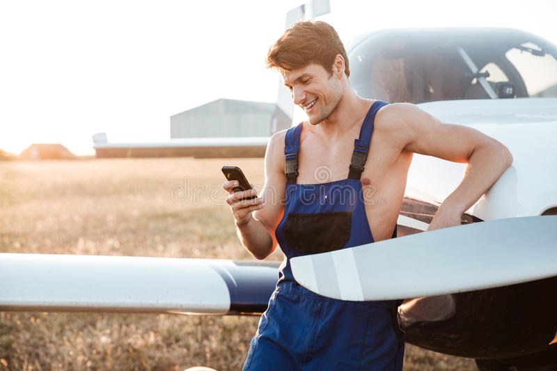 Mecánico joven hermoso en smartphone derecho total del wirh cerca del aeroplano imagen de archivo libre de regalías
