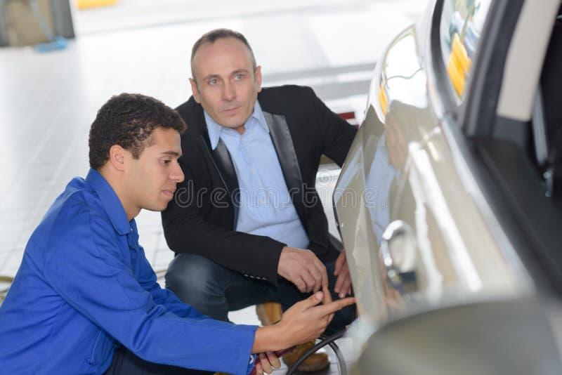 Mecánico joven que habla con el cliente masculino foto de archivo libre de regalías