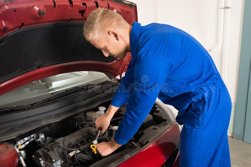 Mecánico joven que repara el coche fotos de archivo