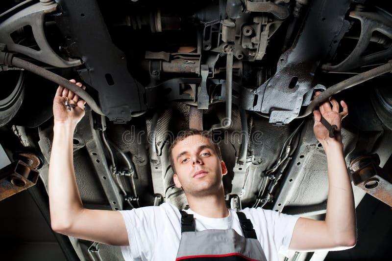 Mecánico joven que trabaja debajo del coche en uniforme fotografía de archivo
