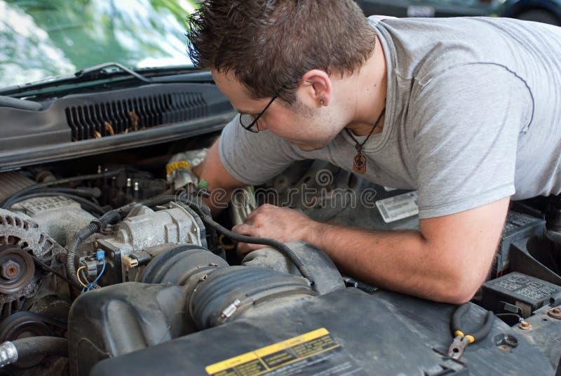 Mecánico joven Working en el motor de coche imagenes de archivo