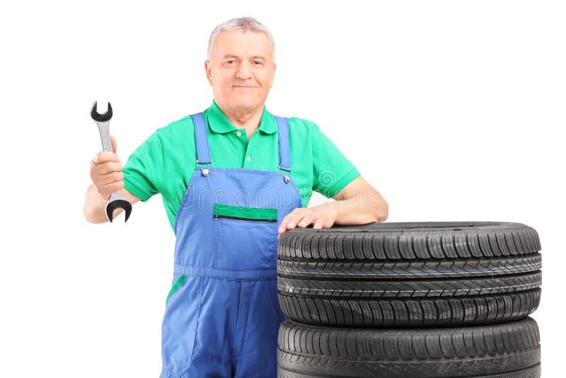 Mecánico maduro que se coloca con los neumáticos de coche y que sostiene una llave foto de archivo