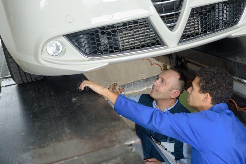 Mecánico And Male Trainee que trabaja por debajo el coche junto fotos de archivo libres de regalías