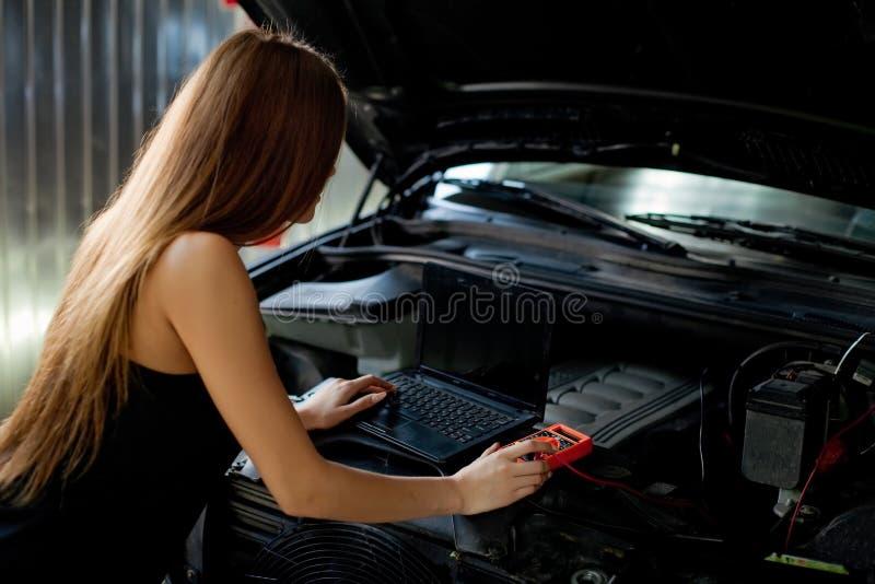 Mecánico moreno atractivo joven en camisa comprobada en garaje Di autos imágenes de archivo libres de regalías