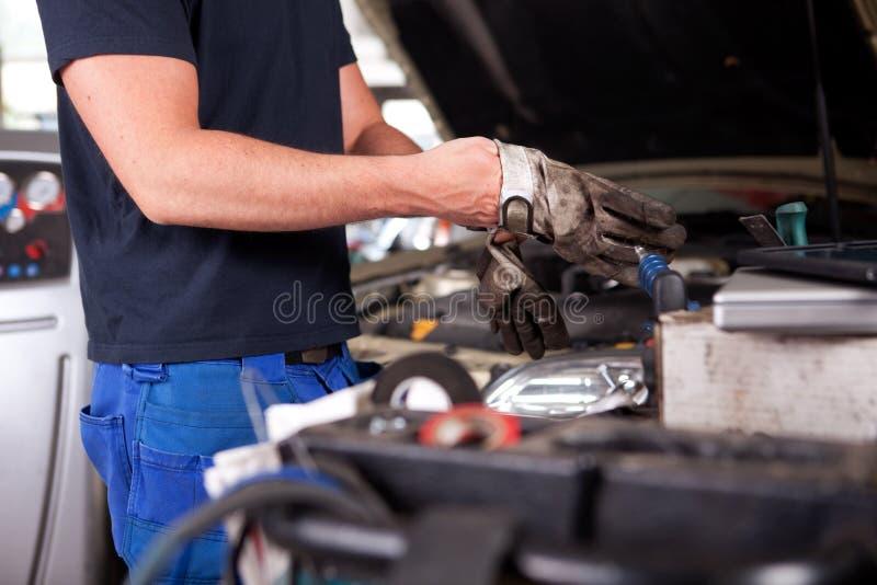 Mecánico Putting en guantes del trabajo imagen de archivo