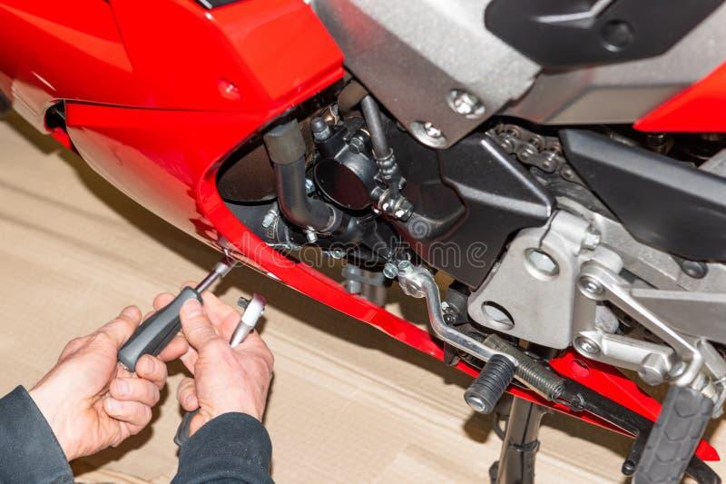 Mecánico que atornilla en el carenado de una motocicleta - taller de la motocicleta de la reparación de Serie imagen de archivo libre de regalías