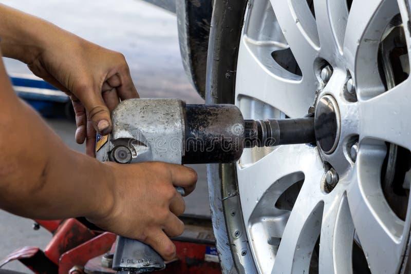 Mecánico que atornilla o que desatornilla la rueda de coche cambiante foto de archivo libre de regalías