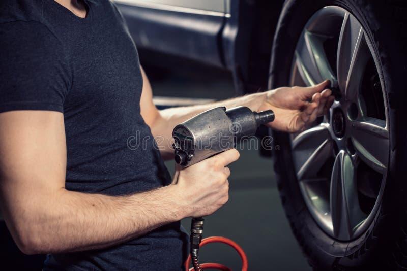 Mecánico que atornilla o que desatornilla la rueda de coche por la llave neumática imágenes de archivo libres de regalías