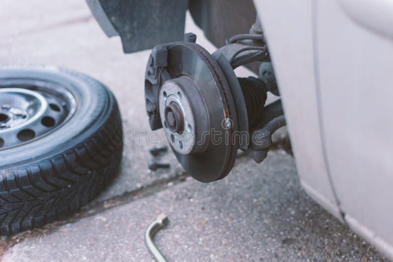 Mecánico que cambia una rueda de un coche imagen de archivo