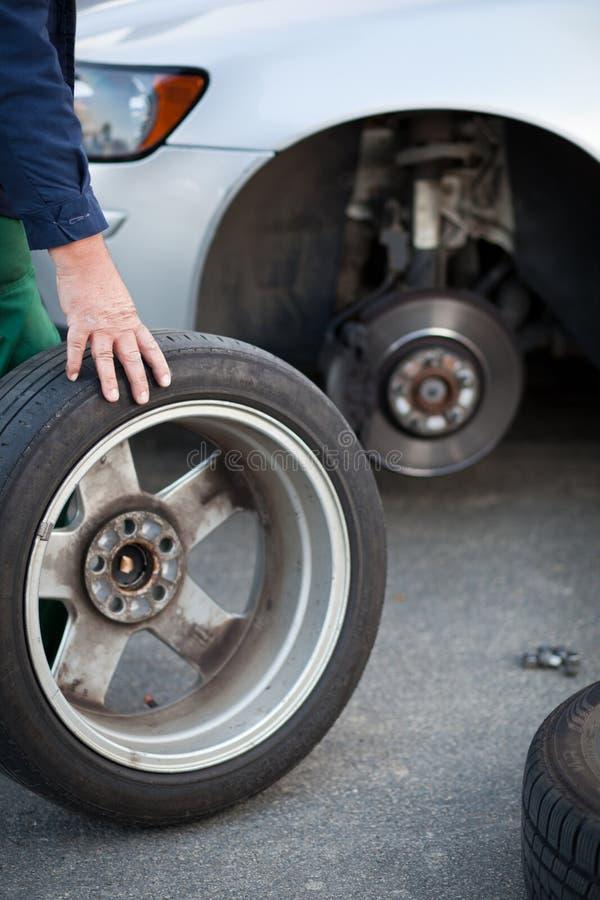 Mecánico que cambia una rueda de un coche moderno fotografía de archivo