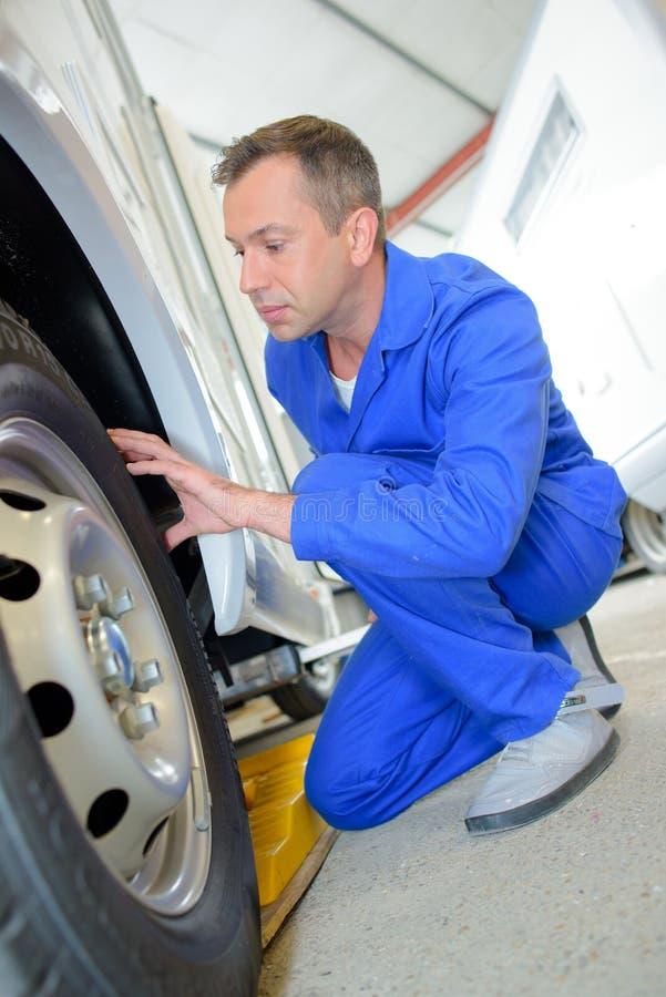 Mecánico que evalúa los neumáticos en la furgoneta foto de archivo libre de regalías
