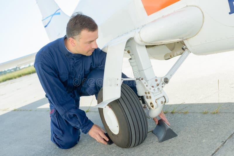 Mecánico que pone las cuñas alrededor de los aviones de la rueda foto de archivo