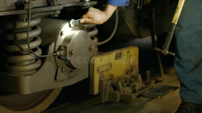 Mec?nico que repara el tren en el dep?sito imagen de archivo