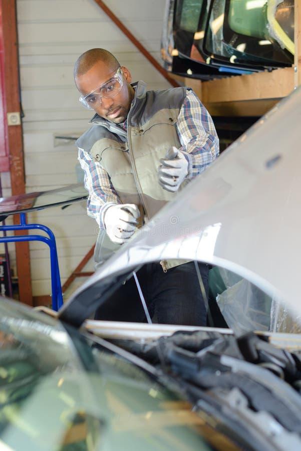 Mecánico que se inclina detrás para mirar el motor de coche imagenes de archivo