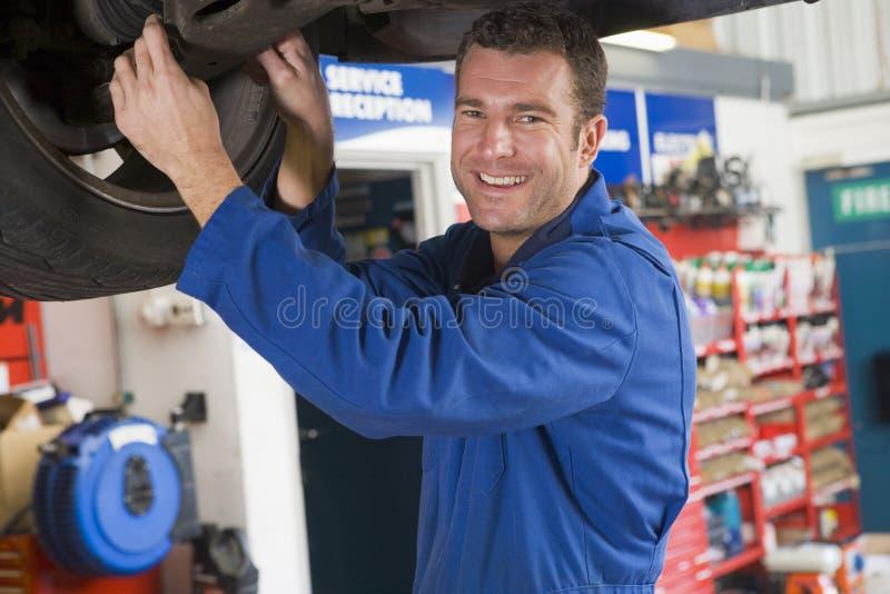 Mecánico que trabaja bajo el coche fotografía de archivo libre de regalías