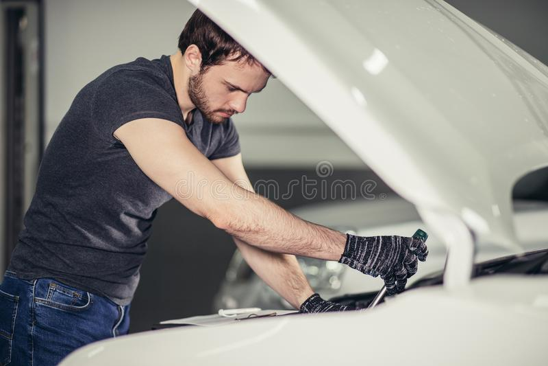 Mecánico que trabaja debajo de la capilla del coche en garaje de la reparación fotos de archivo libres de regalías