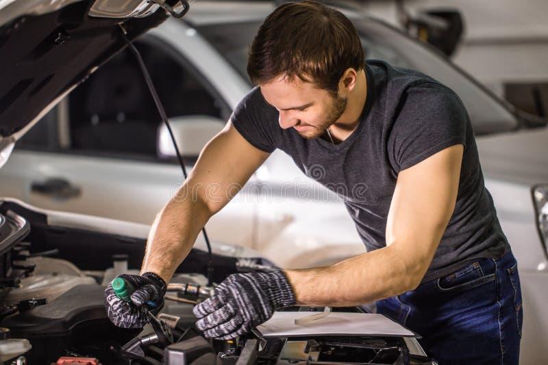 Mecánico que trabaja debajo de la capilla del coche en garaje de la reparación foto de archivo