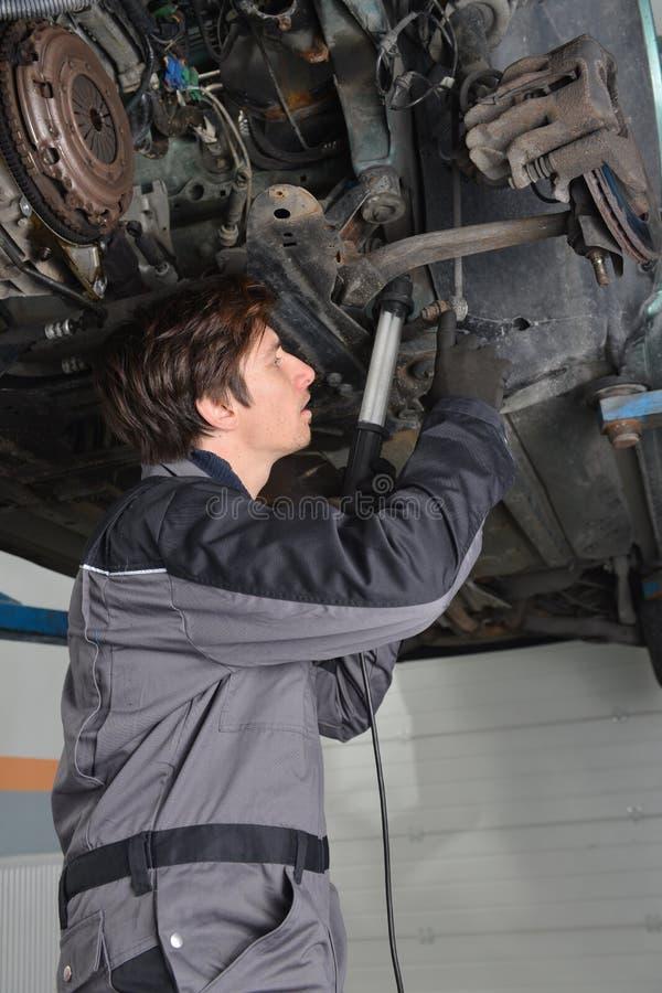Mecánico que trabaja debajo del coche imagen de archivo libre de regalías