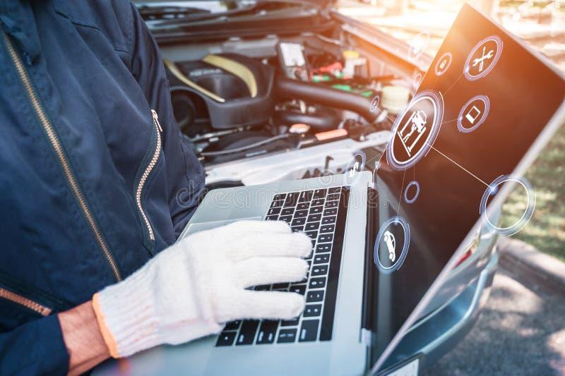 Mecánico que usa el ordenador en fondo del motor con los iconos del servicio del coche servicio del coche y concepto de la compro imágenes de archivo libres de regalías